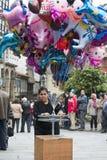 Una mujer que vende los globos en una calle fotografía de archivo