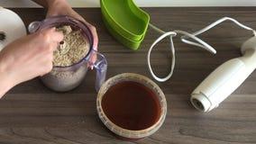 Una mujer quita la tapa de la licuadora y las mezclas con una cuchara tajaron los cacahuetes y las semillas para hacer halva Al l almacen de metraje de vídeo