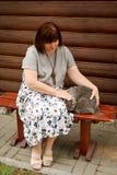 Una mujer regordeta adulta se sienta en un banco cerca de una cabaña de madera y frota ligeramente un gato gris imagen de archivo libre de regalías