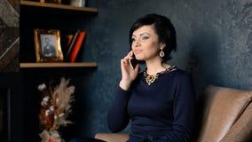 Una mujer rica hermosa llama por el teléfono móvil y habla metrajes