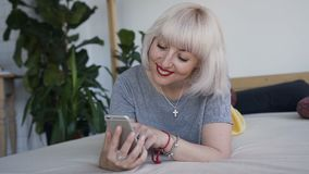 Una mujer rubia con las pecas, mintiendo en una cama grande y mirando el teléfono con una sonrisa almacen de metraje de vídeo