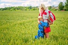 Una mujer rubia con su hijo, vestido en kimono, abrazó cariñosamente el campo de cereales fotos de archivo