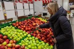 Una mujer rubia en un supermercado compra manzanas del maravillosamente imagen de archivo