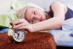 una mujer rubia hermosa miente en la cama con sus ojos abiertos y para el despertador con su mano foto de archivo
