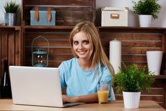 Una mujer rubia hermosa que usa el ordenador portátil adentro imagenes de archivo