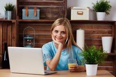 Una mujer rubia hermosa que usa el ordenador portátil adentro fotografía de archivo