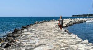 Una mujer rubia joven camina en un embarcadero del mar en la distancia Foto de archivo libre de regalías