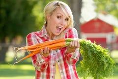 Una mujer rubia joven con las zanahorias Imagen de archivo libre de regalías