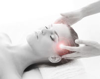 Una mujer rubia joven en un procedimiento principal del masaje Imagenes de archivo