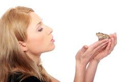 Una mujer rubia joven magnífica que besa una rana Foto de archivo libre de regalías