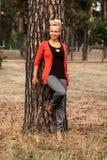 Una mujer rubia joven sonriente se coloca cerca de un árbol de pino en el parque Imagenes de archivo