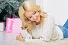Una mujer rubia que desempaqueta Año Nuevo colorido lleno presenta Imagen de archivo