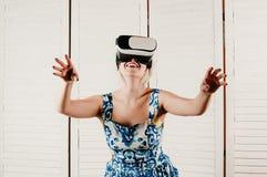 Una mujer rubia que lleva los vidrios de VR, señalando sus manos en el aire fotografía de archivo libre de regalías