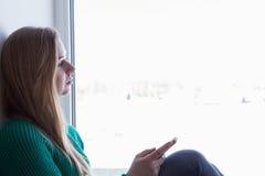 Una mujer rubia que practica surf Internet con su smartphone en el fondo blanco Fotos de archivo libres de regalías
