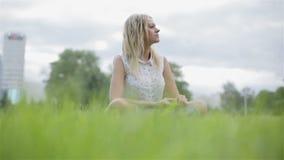 Una mujer rubia que se sienta en una hierba y que mira alrededor metrajes