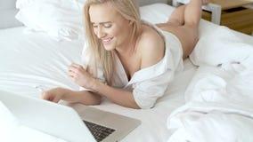 Una mujer rubia sonriente que miente abajo la cama delante de su ordenador port?til metrajes