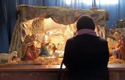 Una mujer ruega delante de las guarderías de la Navidad en la basílica del corazón sagrado en Zagreb Fotos de archivo