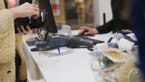 Una mujer saca una tarjeta de su monedero para pagar apagado en una tienda de ropa del ` s de las mujeres Imagenes de archivo