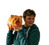 Una mujer sacude una hucha y oye si el dinero está en él foto de archivo