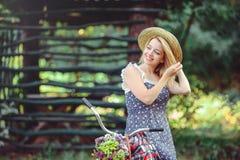 Una mujer sana La muchacha del modelo del verano de la belleza con colores brillantes monta en bicicleta el bosque y la cesta oci Imágenes de archivo libres de regalías