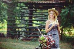 Una mujer sana La muchacha del modelo del verano de la belleza con colores brillantes monta en bicicleta el bosque y la cesta oci Fotos de archivo