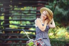 Una mujer sana La muchacha del modelo del verano de la belleza con colores brillantes monta en bicicleta el bosque y la cesta oci Fotos de archivo libres de regalías