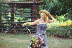 Una mujer sana La muchacha del modelo del verano de la belleza con colores brillantes monta en bicicleta el bosque y la cesta oci Fotografía de archivo