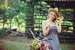 Una mujer sana La muchacha del modelo del verano de la belleza con colores brillantes monta en bicicleta el bosque y la cesta oci Imagen de archivo