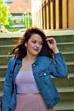 Una mujer satisfecha joven corrige su pelo yendo abajo de las escaleras Foto de archivo libre de regalías