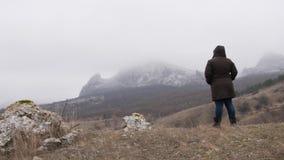Una mujer se acerca al pie de la montaña y para almacen de metraje de vídeo