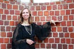 Una mujer se coloca cerca de la pared de ladrillo Foto de archivo libre de regalías