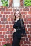 Una mujer se coloca cerca de la pared de ladrillo Imágenes de archivo libres de regalías