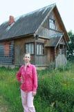 Una mujer se coloca cerca de una casa de madera en el pueblo Fotografía de archivo
