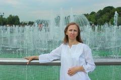 Una mujer se coloca cerca de una fuente Fotografía de archivo libre de regalías
