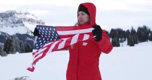 Una mujer se coloca con la bandera americana que agita en un fondo de montañas nevosas en Suiza almacen de metraje de vídeo
