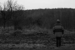 Una mujer se coloca dada vuelta detrás y mira el bosque oscuro foto de archivo