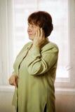 Una mujer se coloca y hablando en el teléfono, mirando con el lado imagen de archivo