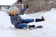 Una mujer se deslizó y se cayó en el camino del invierno Imagenes de archivo