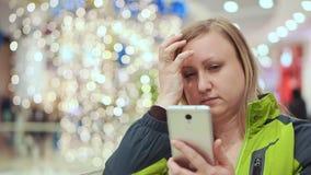 Una mujer se endereza el pelo, mirando el smartphone, ella se coloca en un centro comercial, contra la perspectiva de a almacen de video