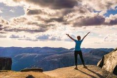 Una mujer se está colocando al borde del acantilado en la manera al canto rodado Foto de archivo libre de regalías