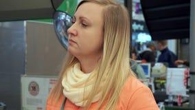 Una mujer se está colocando en línea en la alameda de los cajeros metrajes