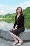 Una mujer se está sentando en el parapeto cerca de la charca Imagen de archivo
