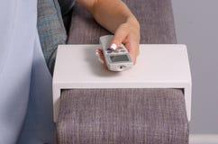 Una mujer se está sentando en el sofá en las manos de un teledirigido de un acondicionador de aire imagenes de archivo