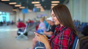 Una mujer se está sentando en el terminal del aeropuerto internacional, esperando su vuelo Utiliza un smartphone Aeropuerto de la almacen de metraje de vídeo