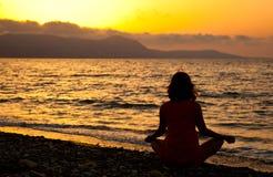 Una mujer se está sentando en la playa Fotografía de archivo libre de regalías