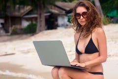 Una mujer se está sentando en la playa con un ordenador portátil foto de archivo