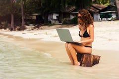 Una mujer se está sentando en la playa con un ordenador portátil imágenes de archivo libres de regalías