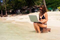 Una mujer se está sentando en la playa con un ordenador portátil imagenes de archivo