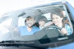 Una mujer se está sentando en la rueda de un nuevo coche Imagen de archivo libre de regalías