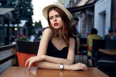 Una mujer se está sentando en un café en la terraza fotos de archivo